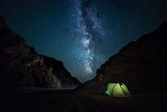 Ravin rocheux de nuit, ciel étoilé avec la manière laiteuse lumineuse un petit camping Images stock