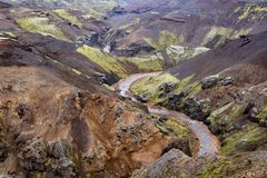 Ravine and river flowing from Kerlingarfjöll, Iceland. Ravine and river flowing from Kerlingarfjöll, Iceland. Steep rocky hills with green grass and black Stock Photos