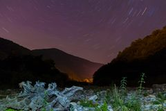 Ravine and star trails at night. Long exposure photo of night landscape of ravine, mountains and star trails, Sochi, Russia Stock Images