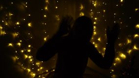 Raving dark shape  of teenager. Outline of dancing girl on new year house party.  Shadow of dancer with garlands on the background. Concept of silhouette stock video footage