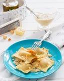 Ravioli blue plate cotton tablecloth hazelnut cheese. Pumpkin blue cheese italian ravioli wine cream sage sauce Royalty Free Stock Images