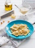 Ravioli blue plate cotton tablecloth hazelnut cheese. Pumpkin blue cheese italian ravioli wine cream sage sauce Stock Photo