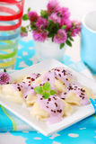 Ravioli with blueberry for child. Sweet ravioli stuffed with cottage cheese and poured blueberry yogurt for child Stock Photos