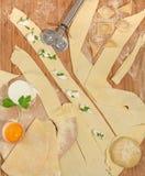 Ravioli casalinghi italiani con la ricotta, la farina, l'uovo, la pasta cruda e le erbe aromatiche, disposti su una tavola di leg Fotografia Stock