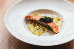 Ravioli in cream sauce with Grilled Salmon topping with Caviar.  royalty free stock photography