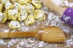 Ravioli crudi gialli con farina, la spatola ed il tuffatore sul legno immagini stock