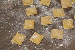 Ravioli crus savoureux avec de la farine sur le fond en bois Processus de faire les ravioli italiens image libre de droits