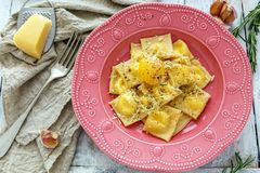 Ravioli with egg yolk, black pepper and parmesan. Homemade ravioli with egg yolk and parmesan in a bowl on white wooden table Stock Images