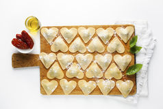 Ravioli in a heart shape. cutting board with a group of raw fres Stock Photos