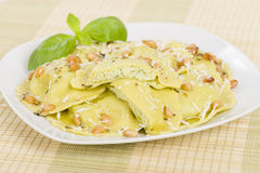 Ravioli. Italian egg and spinach pasta with basil, ricotta and pine nuts filling with brown butter, pine nuts and sage sauce. Served with crusty bread Stock Photography