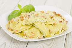 Ravioli. Italian egg and spinach pasta with basil, ricotta and pine nuts filling with brown butter, pine nuts and sage sauce. Served with crusty bread Royalty Free Stock Photos
