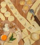 Ravioli italiani casalinghi con gorgonzola, le noci, la farina, l'uovo, la pasta cruda e le erbe aromatiche, disposti su una tavo Fotografia Stock