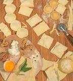 Ravioli italiani casalinghi con gorgonzola, le noci, la farina, l'uovo, la pasta cruda e le erbe aromatiche, disposti su una tavo Fotografia Stock Libera da Diritti