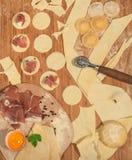 Ravioli italiano caseiro com o prosciutto, a farinha, o ovo, massa crua e as ervas aromáticas, colocados em uma tabela de madeira Imagem de Stock