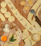 Ravioli italiens faits maison avec Gorgonzola, noix, farine, oeuf, pâte crue et herbes aromatiques, placés sur une table en bois  Photographie stock