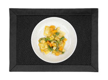 Ravioli meal on plate atop place mat Stock Images