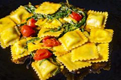 Ravioli met spinazie en gestoofde kersentomaten stock afbeeldingen