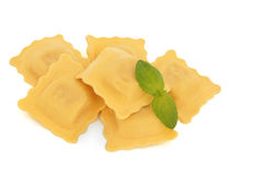 Ravioli Pasta. Stack with basil herb leaf sprig isolated over white background. Selective focus Royalty Free Stock Image