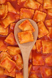 Ravioli Pasta. In tomato sauce on a wooden spoon and forming a background Stock Image
