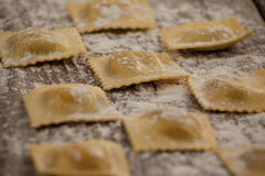 Ravioli pasta dusted with floor on wooden background Stock Photos