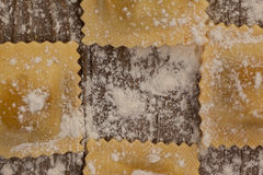 Ravioli pasta dusted with floor on wooden background Stock Photo