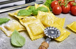 Ravioli pasta, homemade pasta and pasta roller. On a stone background. Italian cuisine, fresh pasta cooking Royalty Free Stock Image