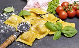 Ravioli pasta, homemade pasta and pasta roller. On a stone background. Italian cuisine, fresh pasta cooking Stock Images