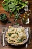 Ravioli pronti in un piatto, spinaci, olio d'oliva in un barattolo Immagine Stock