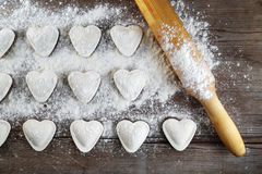 Ravioli and rolling pin. Heart shaped ravioli with flou and rolling pin, on vintage wood table background. Cooking dumplings. Top view Royalty Free Stock Image