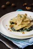 Ravioli with spinach, ricotta and nutmeg. On a white plate on a dark wooden background stock images
