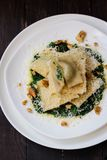 Ravioli with spinach, ricotta and nutmeg. On a white plate on a dark wooden background Stock Photo