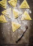 Ravioli  Triangoli making, preparation on rustic wooden background, top view. Royalty Free Stock Image