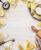 Ravioli triangoli making, preparation on white wooden background, top view, frame. Royalty Free Stock Photography