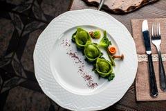 Ravioli verde com ovo de codorniz em um fundo preto Uma festa de Dia das Bruxas fotos de stock