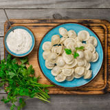 Ravioli on the wooden board with sauce and parsley. Top view Stock Photo