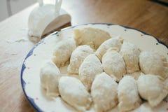 Raviolis, bolas de masa hervida o pelmeni hechas en casa frescas cubiertos en harina en una tabla de madera Crudo, crudo Fotos de archivo libres de regalías
