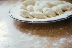 Raviolis, bolas de masa hervida o pelmeni hechas en casa frescas cubiertos en harina en una tabla de madera Crudo, crudo Fotografía de archivo