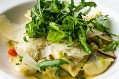 Raviolis con el queso parmesano y el Arugula en cuenco Fotos de archivo
