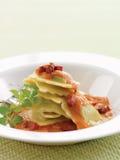 Raviolis con la salsa color de rosa cremosa del pancetta Imagenes de archivo