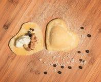 Raviolis hechos en casa crudos dos, abierto y cerrado, en la forma del corazón, cubierto con la harina y puesto en la tabla de ma Imagen de archivo libre de regalías