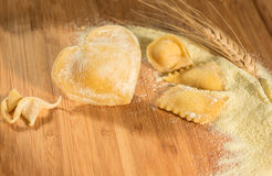 Raviolis hechos en casa en la forma del corazón con un oído del trigo, del tortellini italiano, de la harina y de una pasta cruda Fotos de archivo