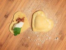 Raviolis hechos a mano crudos dos, abierto y cerrado, en la forma del corazón, cubierto con la harina y puesto en la tabla de mad Foto de archivo