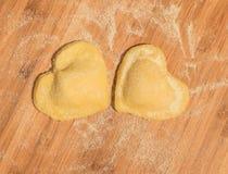 Raviolis hechos a mano crudos dos en la forma del corazón, cubierto con la harina y puesto en la tabla de madera Imagen de archivo libre de regalías