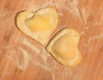Raviolis hechos a mano crudos dos en la forma del corazón, cubierto con la harina y puesto en la tabla de madera Fotografía de archivo libre de regalías