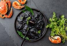 Raviolis negros italianos con los camarones y los cangrejos de los mariscos en la placa negra, fondo de piedra gris de la pizarra Imagenes de archivo