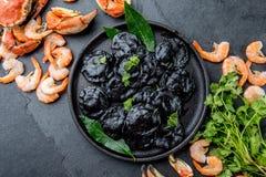 Raviolis negros italianos con los camarones y los cangrejos de los mariscos en la placa negra, fondo de piedra gris de la pizarra Imágenes de archivo libres de regalías