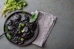 Raviolis negros italianos tradicionales en la placa negra, fondo de piedra gris de la pizarra Visión superior Imagenes de archivo