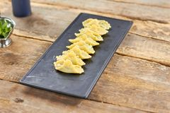 Raviolis in a row on black rectangle plate. Dumpling on a black plate Stock Images