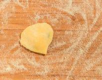 Raviolo με μορφή της καρδιάς, που καλύπτεται με το αλεύρι και που τοποθετείται στον ξύλινο πίνακα Στοκ Φωτογραφία