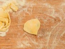 Raviolo με μορφή της καρδιάς, που καλύπτεται με το αλεύρι και που τοποθετείται στον ξύλινο πίνακα Στοκ Φωτογραφίες